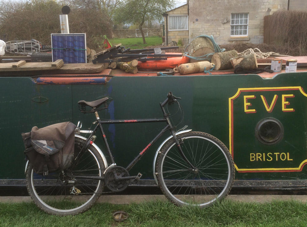 Bicycle propped up against a narrowboat called Eve